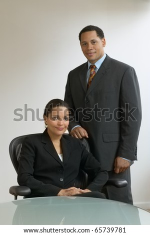 Portrait of a businesswoman sitting and a businessman standing - stock photo