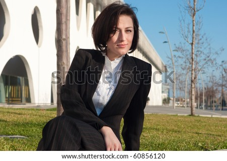 Portrait of a businesswoman sitting and posing outdoors - stock photo