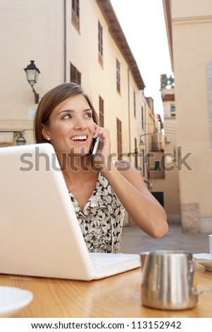 Portrait of a businesswoman using a cell phone and a laptop computer while sitting down at a coffee shop table outdoors.