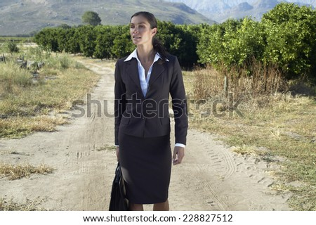 Portrait of a businesswoman walking down a dirt road in rural setting