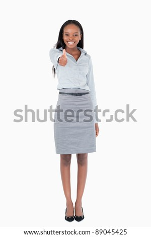 Portrait of a businesswoman with her thumb up against a white background