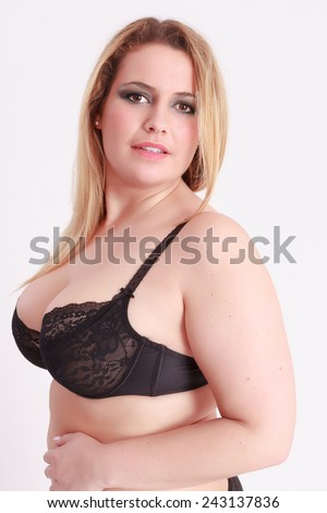 Portrait of a Busty girl in bra with smooth blond long hair looks in the camera / Busty girl in bra with smooth blond long hair - stock photo