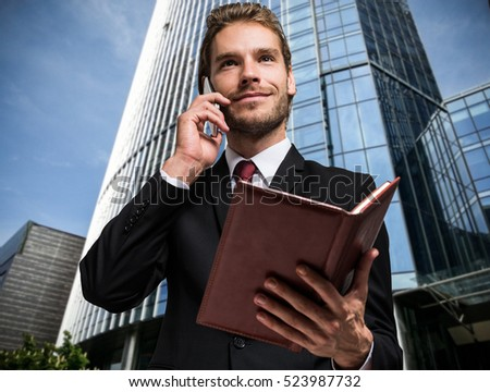 Portrait of a busy businessman using his mobile phone while holding an agenda