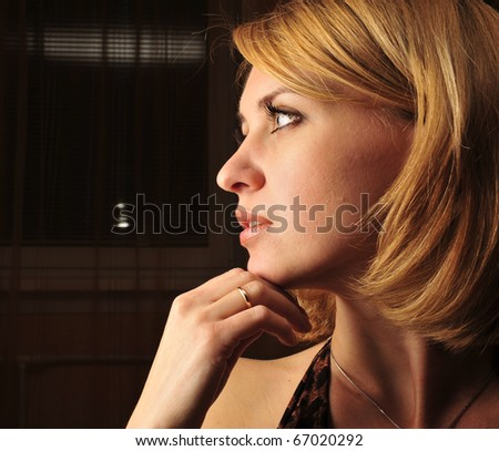 Portrait of a calm young woman sitting inside dark room with romantic light - stock photo