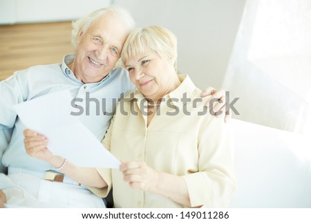 Portrait of a candid senior couple reading letter at home - stock photo