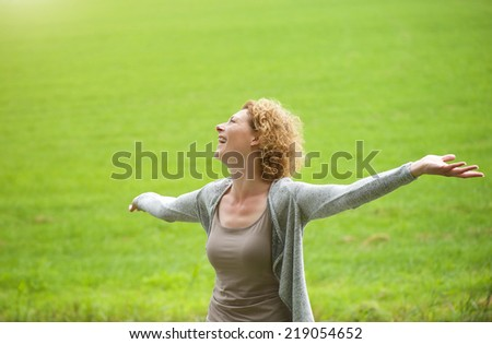 Portrait of a carefree older woman enjoying the outdoors with arms spread open - stock photo