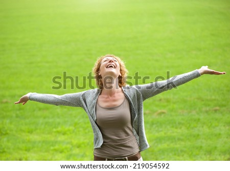 Portrait of a carefree older woman smiling with arms open - stock photo