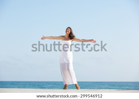 Portrait of a carefree woman enjoying life, standing outdoors with arms outstretched - stock photo