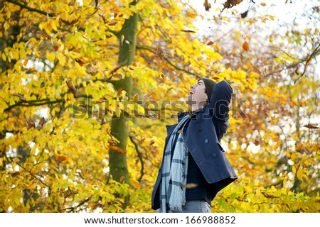 Portrait of a carefree young man standing outside looking up - stock photo