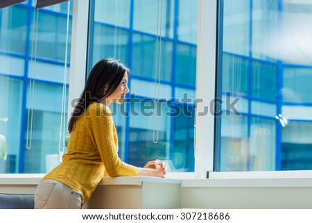 Portrait of a casual businesswoman looking at window in office  - stock photo