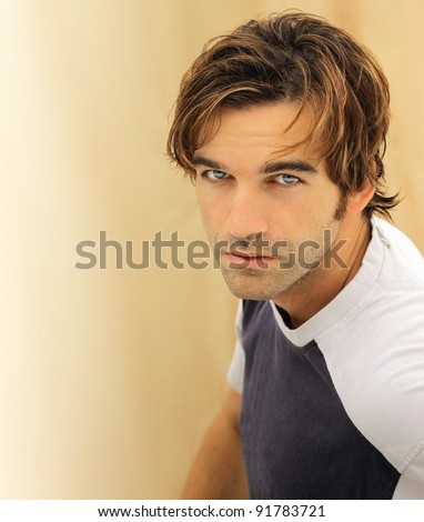 Portrait of a casual good looking male model with striking blue eyes - stock photo