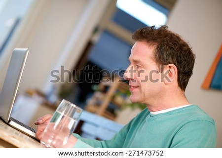 Portrait of a casual man working on laptop at home - stock photo