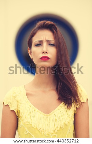 Portrait of a casual pretty disappointed woman over nimbus symbol above head. Close up. Retro, vintage style. Outdoor shot - stock photo