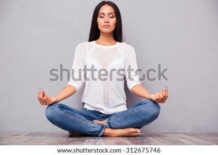 Portrait of a casual pretty woman meditating on the floor on gray background - stock photo
