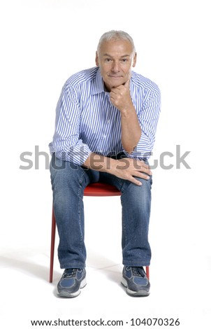 Portrait of a casual senior sitting on a red chair on white background. - stock photo