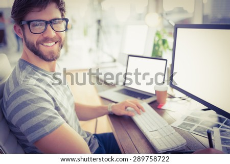 Portrait of a casual young businessman using computer in office - stock photo