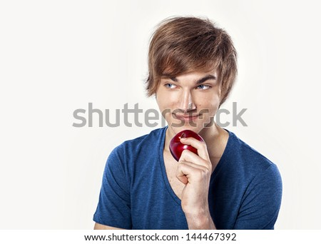 Portrait of a casual young man with a happy face holding a apple, against a white wall