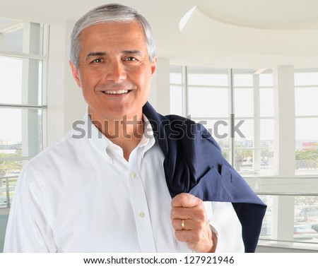 Portrait of a casually dressed businessman in a modern office building. Man is smiling holding his jacket over his shoulder. - stock photo