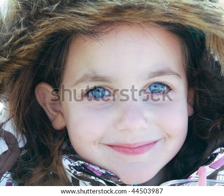 portrait of a caucasian pretty girl with blue eyes dressed up for cold weather - stock photo
