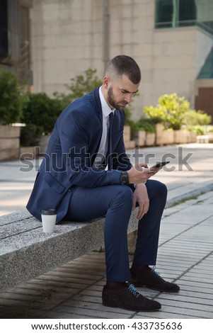 Portrait of a caucasian young businessman looking at smart phone outside the office seated on a bench. Coffee break time - stock photo