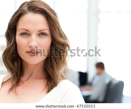 Portrait of a charismatic woman at a meeting while her team working in the background - stock photo