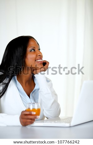 Portrait of a charming and relaxed woman holding an orange juice while looking up in front a laptop at home indoor - stock photo