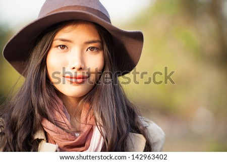 Portrait of a charming Asian woman wearing a hat on an autumn day.