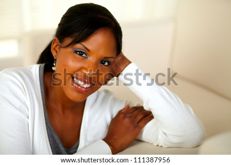 Portrait of a charming black female looking and smiling at you. With Copyspace
