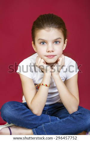 Portrait of a charming brunette little girl looking at camera, isolated on red background