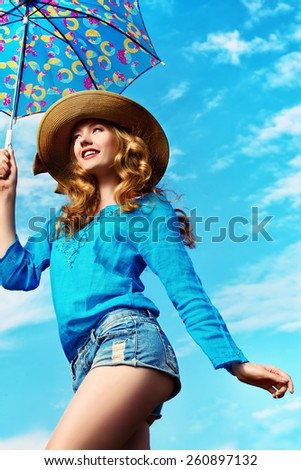 Portrait of a charming girl in elegant hat against the blue sky. - stock photo