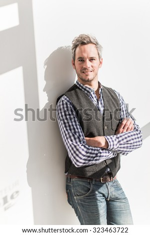 Portrait of a charming grey hair man with beard standing and leaning against a white wall. He is wearing a checkered blue shirt and jeans. He is looking at camera with confidence, his arms crossed - stock photo