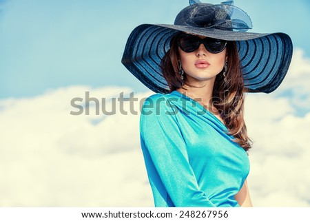 Portrait of a charming lady in beautiful elegant dress and hat against the sky.
