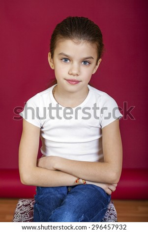 Portrait of a charming little girl looking at camera, isolated on red background - stock photo
