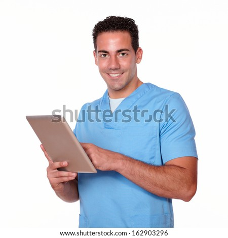 Portrait of a charming nurse man on blue uniform using his tablet pc while smiling and looking at you on isolated studio - stock photo