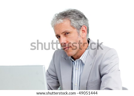 Portrait of a charming senior businessman working at a laptop
