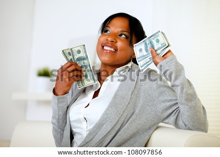 Portrait of a charming woman looking up and holding plenty of cash money at home indoor - stock photo