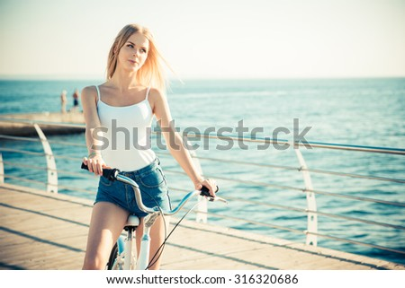 Portrait of a charming woman riding on bicycle outdoors near the sea - stock photo