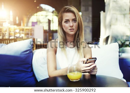 Portrait of a charming woman using mobile phone during breakfast in coffee shop interior in summer day, young female student holding her cell telephone while sitting in modern restaurant during lunch - stock photo