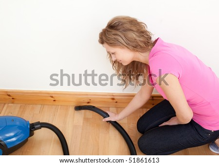 Portrait of a charming woman vacuuming at home - stock photo