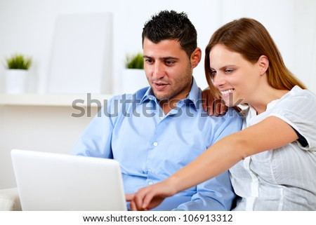 Portrait of a charming young couple sitting on sofa using laptop at home indoor - stock photo