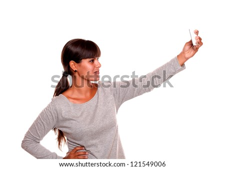 Portrait of a charming young woman taking a photo with cellphone against white background - stock photo