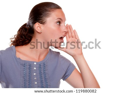 Portrait of a charming young woman whisper a secret on blue shirt standing over white background with copyspace - stock photo