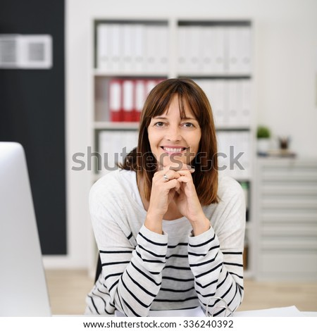 Portrait of a Cheer Office Woman Sitting at her Table, Leaning on her Elbows and Smiling at the Camera. - stock photo