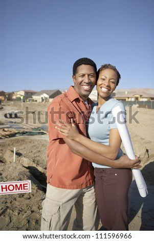 Portrait of a cheerful African American couple embracing at a construction site
