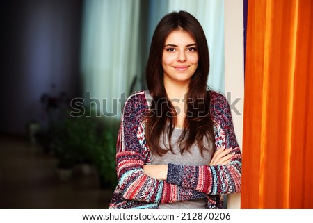 Portrait of a cheerful attractive woman standing with arms folded at home