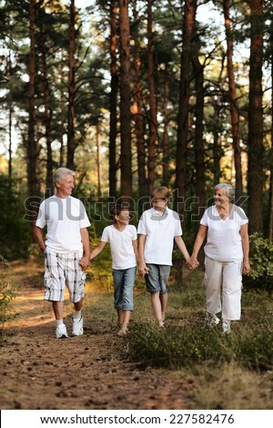 Portrait of a cheerful boys with grandparents having fun in summer forest - stock photo