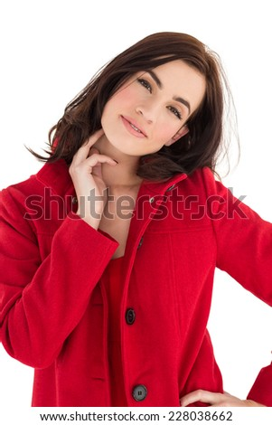 Portrait of a cheerful brunette in red coat on white background - stock photo