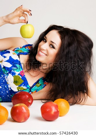 Portrait of a cheerful brunette with fresh fruits on the floor
