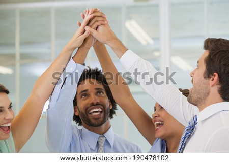 Portrait of a cheerful business team joining hands together in bright office - stock photo