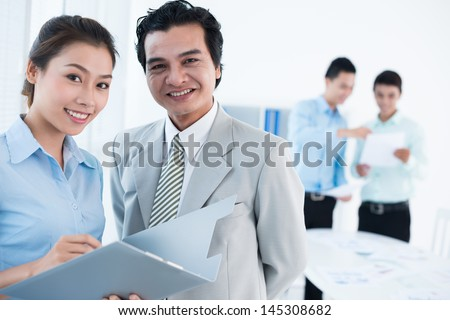 Portrait of a cheerful business team smiling and looking at camera - stock photo